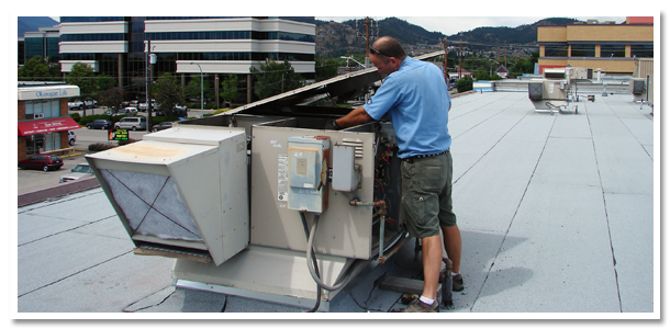worker repairing cooling unit on roof